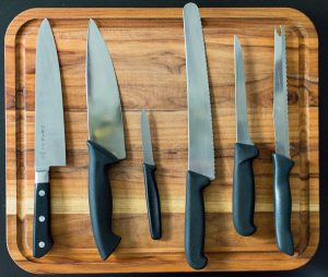 Knives on a wooden cutting board.