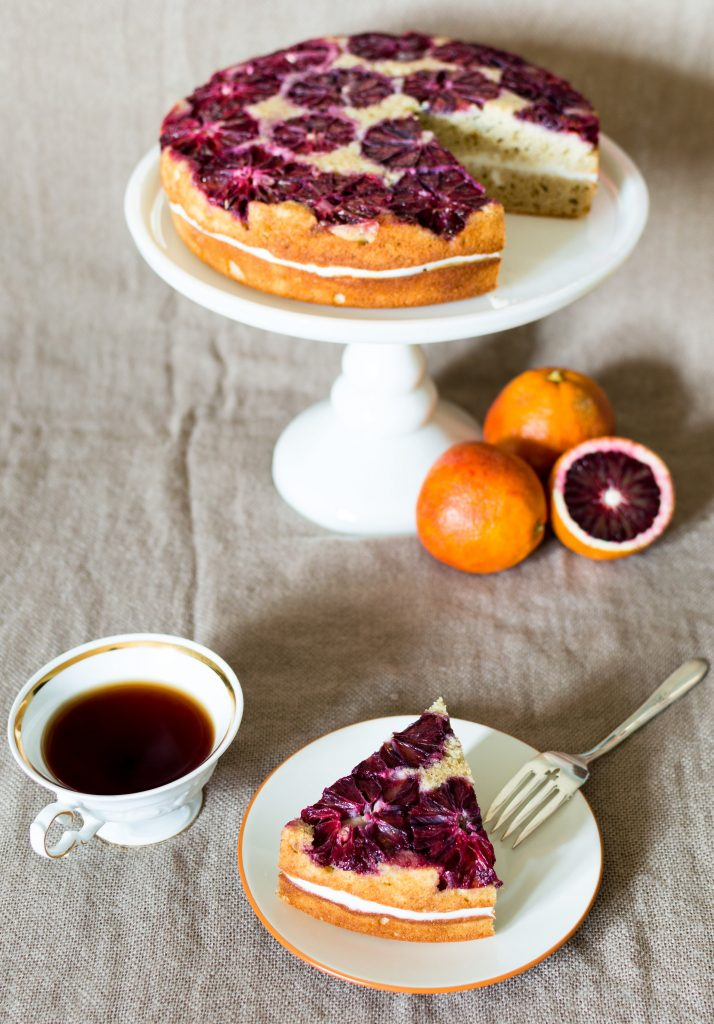 blood orange spice cake on white cake stand with tea and oranges