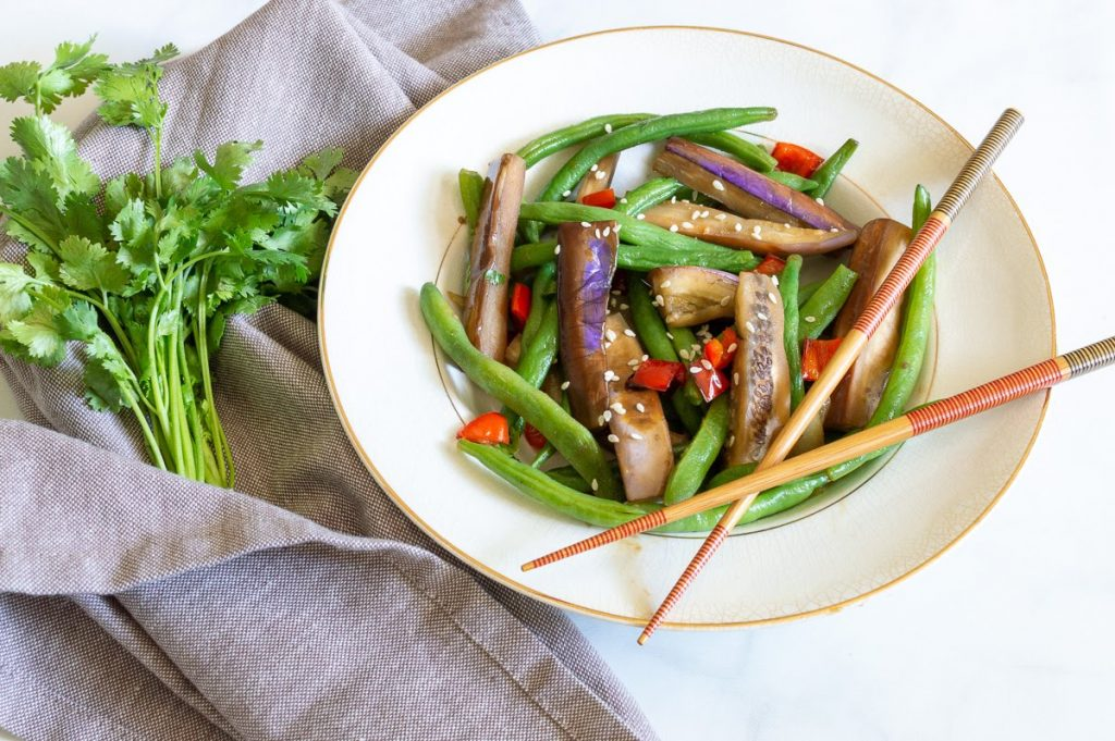Eggplant, green beans, and red peppers in a white bowl with chopsticks. Garnished with sesame seeds and a bunch of cilantro on a grey napkin.