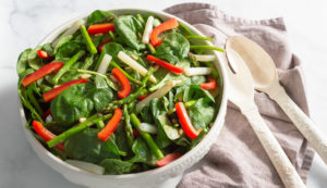 Asparagus and red pepper salad in a white salad bowl with a gray napkin and white utensils.