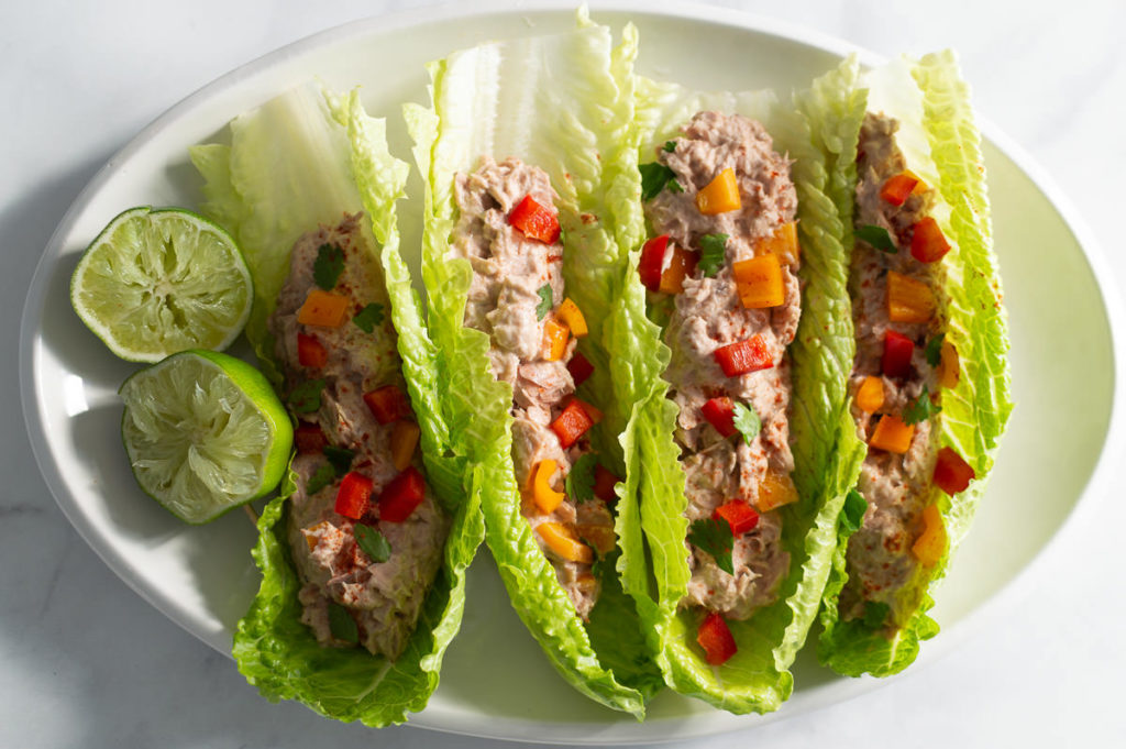 Fiesta tuna salad in romaine lettuce boats on a white plate.