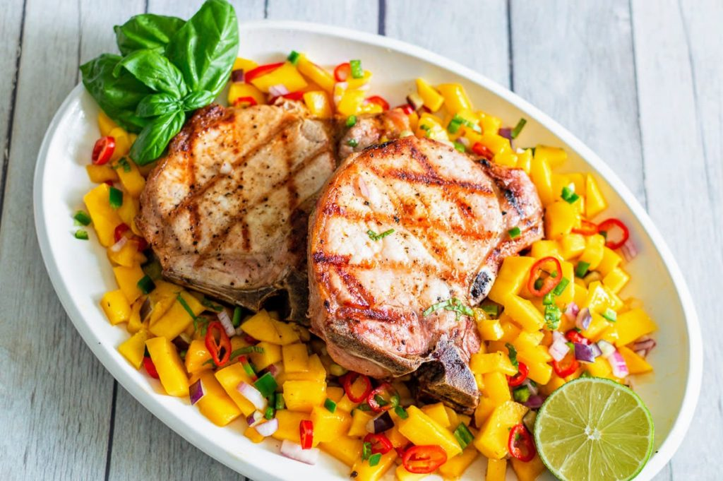 Grilled pork chops on a white plate with mango salsa.