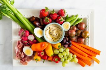 Paleo vegetable platter with peppers, carrots, celery, tomatoes, grapes, strawberries on a white platter.