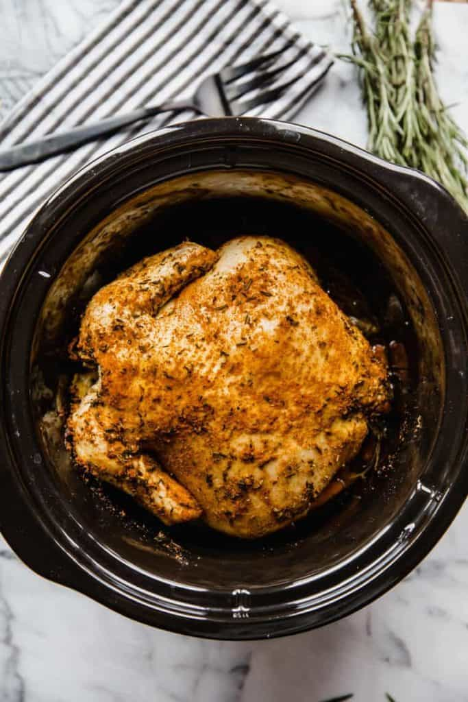 Whole chicken in a slow cooker with rosemary seasonings.
