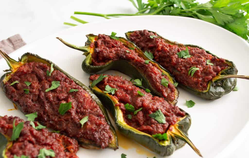 Poblano peppers stuffed with chorizo filling on a white platter, garnished with cilantro.